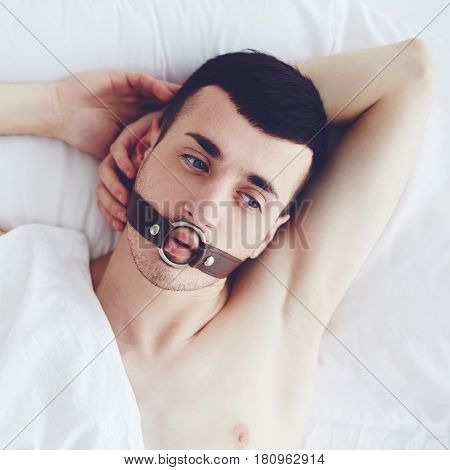 handsome man with a face strap laying in bed stock photo