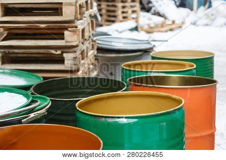 Old empty colored tin barrels from gasoline, oil/ vintage cask, rusted tins, cans with chemicals, industry oil barrels, chemical tank, hazardous waste, chemical reagents, ecological concept. stock photo