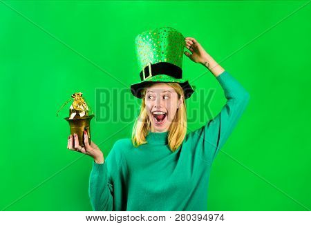 Happy smiling girl in Leprechaun costume holds pot with gold. Green hat. Leprechaun hold pot with gold. Green leprechaun. Hat with clover. Saint Patrick's Day. Irish Traditions. Saint Patrick. stock photo