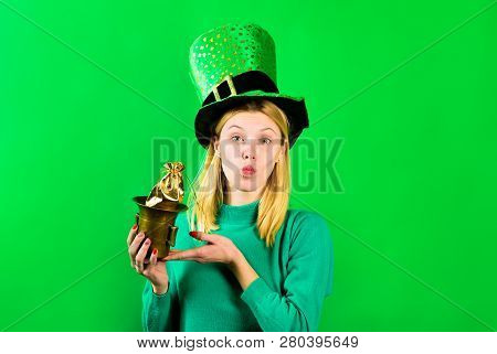 Pretty blonde girl in Leprechaun costume holds pot with gold. Green hat. Leprechaun hold pot with gold. Green leprechaun. Hat with clover. Saint Patrick's Day. Irish Traditions. Saint Patrick. Kiss. stock photo