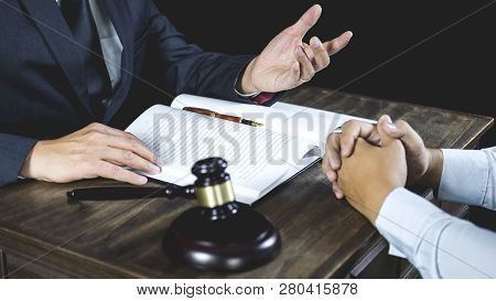 Meeting and collaboration concept, Businessman and Male lawyer or judge consult having team meeting with client discussing of contract in courtroom. stock photo