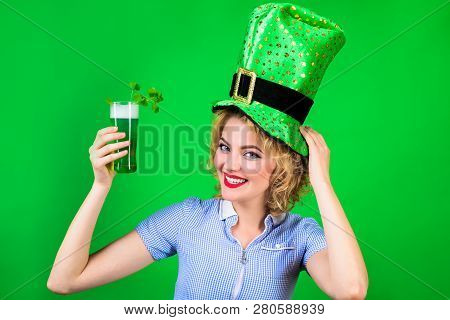 Green top hat. Saint Patrick's Day. St Patricks Day. Woman in top hat holds green beer. Leprechaun. Green beer. Irish Traditions. Pub. Woman drinking in Irish pub. Spring holidays. stock photo