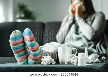 Sick Woman With Flu, Cold, Fever And Cough Sitting On Couch At Home. Ill Person Blowing Nose And Sne
