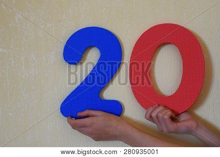 20 - hands holding colorful number two and zero or twenty on mild yellow wall background with copy space for text. 20th anniversary or birthday design. stock photo