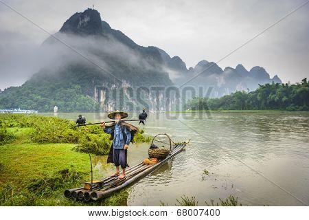 Cormorant fisherman and his birds on the li river in yangshuo, guangxi, china.