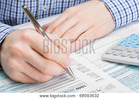 Male filling out 1040 United States of America Tax Form - studio shot stock photo