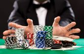 club, betting, individuals and stimulation idea - close up of poker player with chips, cash and
