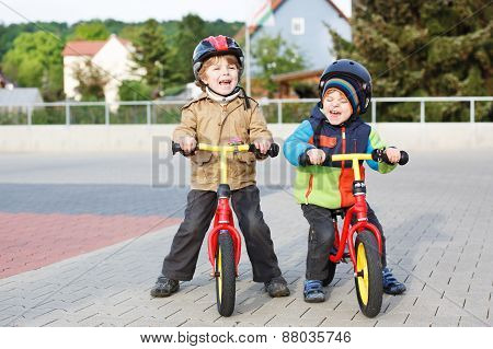 Two little siblings children having fun on bikes in city on vacations outdoors. stock photo