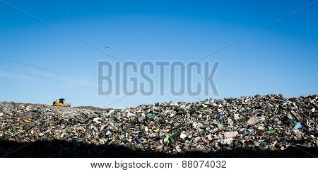 Landfill with bulldozer working against beautiful blue sky full of sea birds. Great for environment and ecological themes stock photo