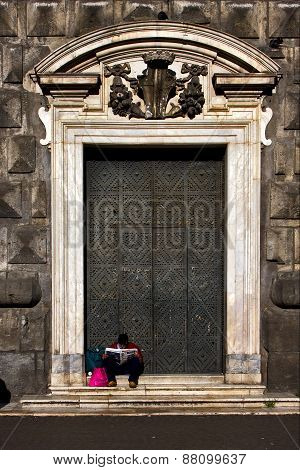 the brown gate in the church gesu nuovo in naples and a homeless reading a newspaper stock photo