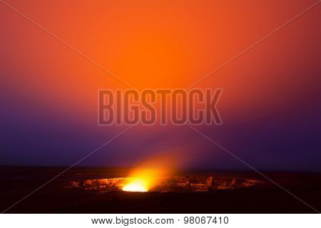 A 30-minute exposure at 3am of the glowing lava lake in the caldera of Hawaii's Kilauea Volcano bounces light off of the haze drifting by in the sky.  stock photo