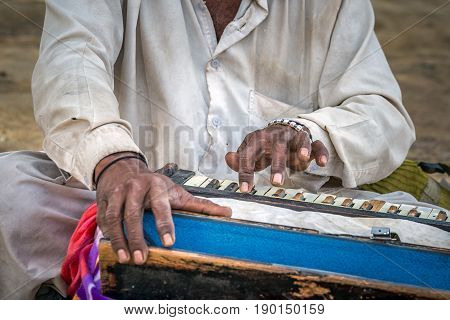A old man is playing indian traditional musical instruments for kirtan harmonium. stock photo