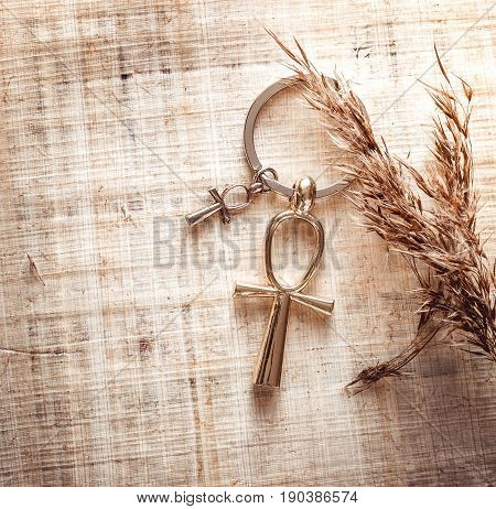 Egyptian cross ankh with long shadow on a sunny day against a background of papyrus. Photo toned. stock photo