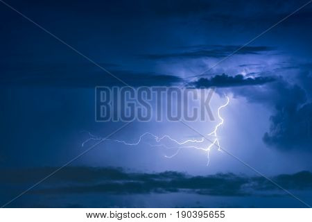 Thunder storm lightning strike on the dark cloudy sky background at night. stock photo