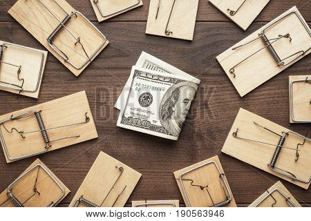 many mousetraps and money business concept. mousetraps surrounding money. starting business concept with money and traps near it. hard to earn money business concept. new business concept on brown wooden table.