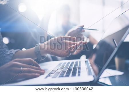 Business meeting concept.Closeup view of business people working with mobile computer at modern office.Analyze business plans, using laptop.Blurred background.Cropped