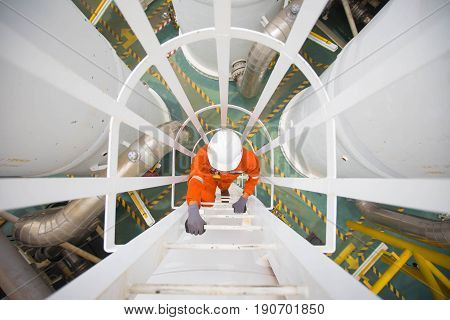 Process engineer climb up to the top of gas dehydration vessel to inspect and check abnormal condition of process in the oil and gas central processing platform.