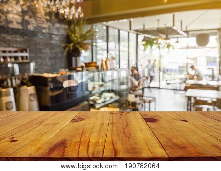 Wooden board empty table in front of blurred background. Perspective brown wood over blur in coffee shop or cafe and restaurant- can be used for display or montage your products.Mock up your products.