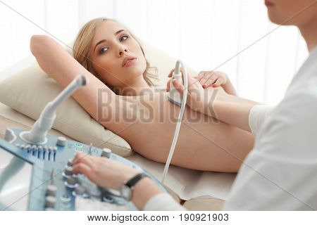 Young woman getting breast examination by her gynecologist ultrasound scanning sonography technology medical equipment healthcare. stock photo