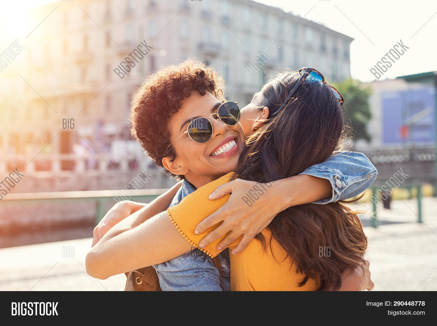 Happy meeting of two friends hugging in the street. Smiling girls friends laughing and hugging in th
