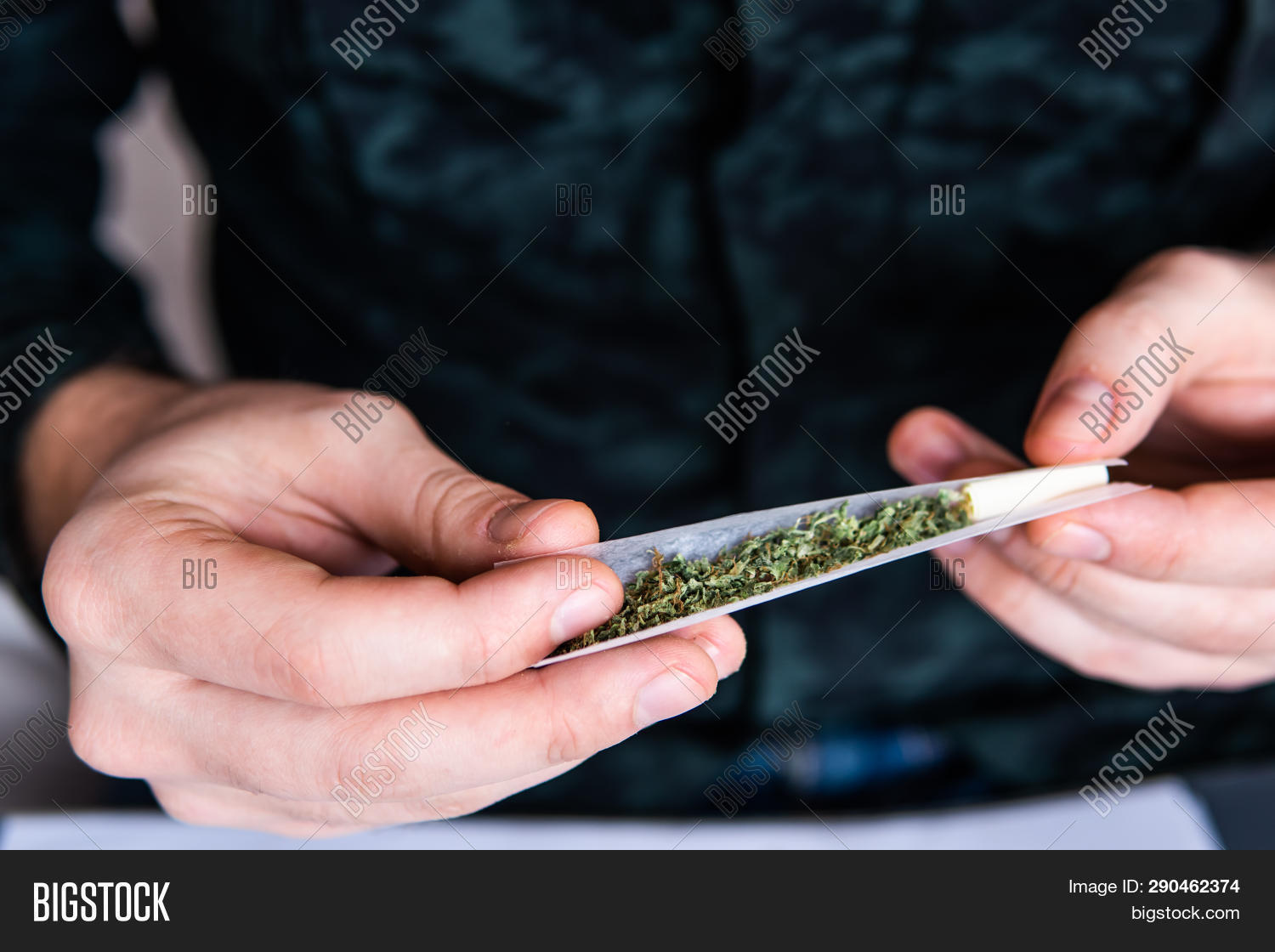 Drug Use. Close Up . Man Rolling A Marijuana Joint. Man Preparing And Rolling Marijuana Cannabis Joi