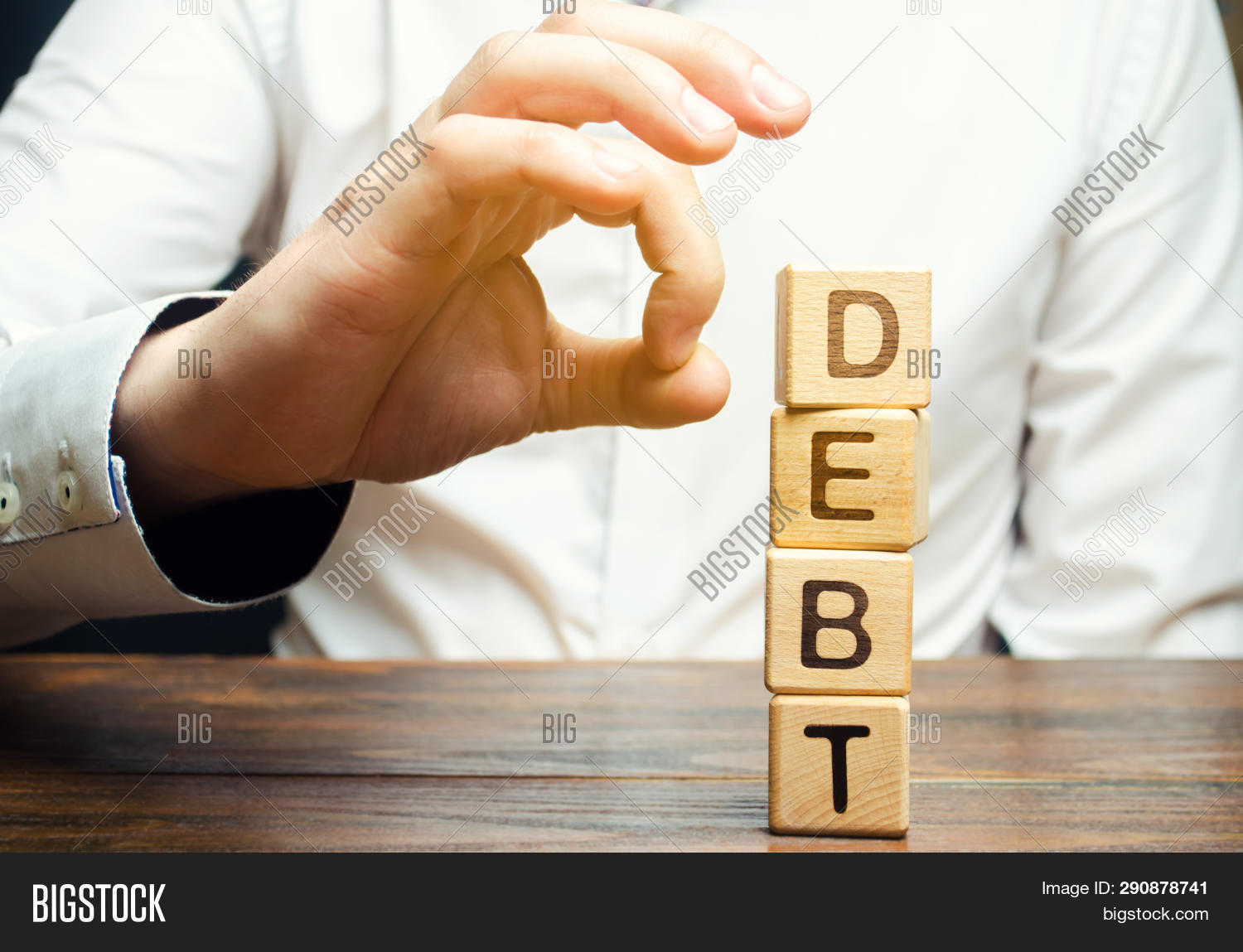 Businessman Removes Wooden Blocks With The Word Debt. Reduction Or Restructuring Of Debt. Bankruptcy