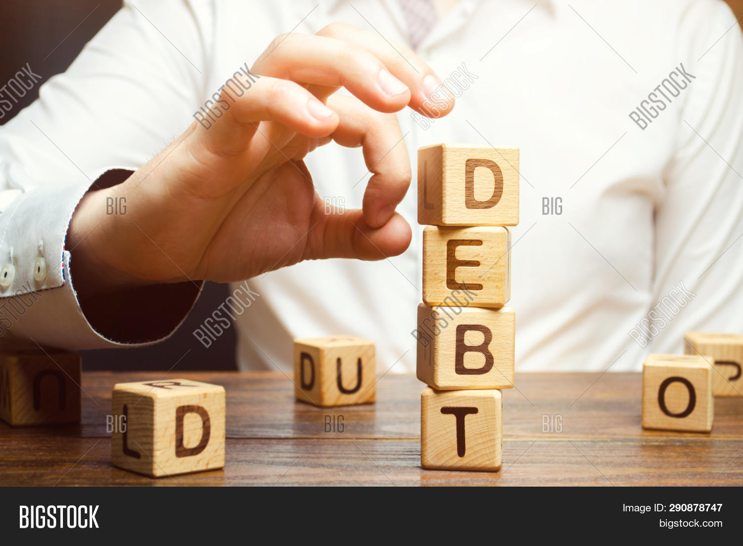Businessman removes wooden blocks with the word Debt. Reduction or restructuring of debt. Bankruptcy announcement. Refusal to pay debts or loans and invalidate them. Debts service relief