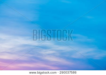 Sunset sky with pink lilac light clouds. Colorful smooth blue white sky gradient. Natural sunrise background. Amazing heaven at morning. Slightly cloudy evening atmosphere. Wonderful weather on dawn. stock photo