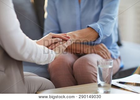 Young professional counselor holding hand of mature woman while giving her advice and supporting her stock photo