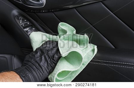 A man cleaning car seat with blue microfiber cloth. Car detailing or valeting concept. Selective focus. Car detailing. Cleaning with sponge. Worker cleaning. Car wash concept solution to clean stock photo