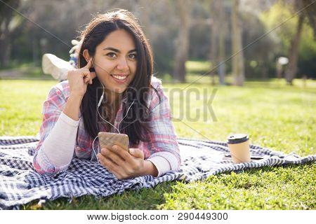 Happy Positive Girl Enjoying Favorite Music. Young Woman In Earphones Resting On Grass In Park And L