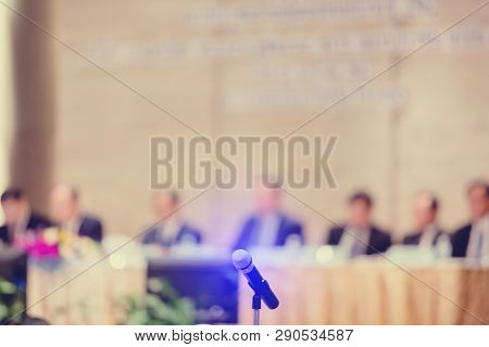 Blurry of microphone with chairman of the meeting and executive committee background in auditorium for shareholders meeting or seminar event, Annual shareholder meeting stock photo