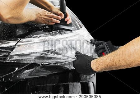 Car wrapping specialist putting vinyl foil or film on car. Protective film on the car. Applying a protective film to the car with tools. Car detailing. Transparent film. Car paint protection. Trimming stock photo