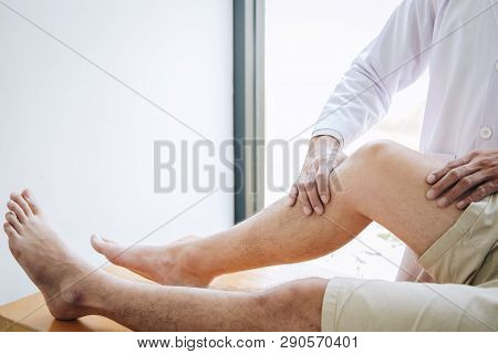 Doctor physiotherapist assisting a male patient while giving exercising treatment massaging the leg of patient in a physio room, rehabilitation physiotherapy concept. stock photo