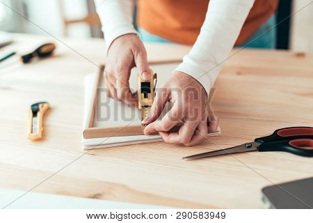 Female carpenter tape measuring picture frame in small business woodwork workshop, close up of hands stock photo