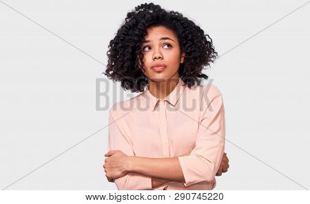 Thoughtful African American woman has thinking expression, looking up away to the blank copy space. Doubtful dark skinned female can`t make choice, has questioned expression, isolated on white. stock photo