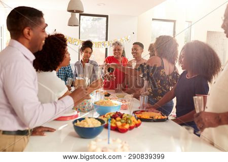 Millennial black woman pouring champagne during a three generation family celebration at home stock photo