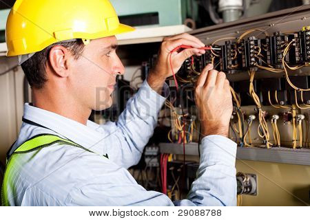 male electrician testing industrial machine stock photo