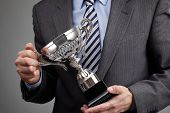 Businessman celebrating with trophy honor for achievement in business or ahead of all comers brandis