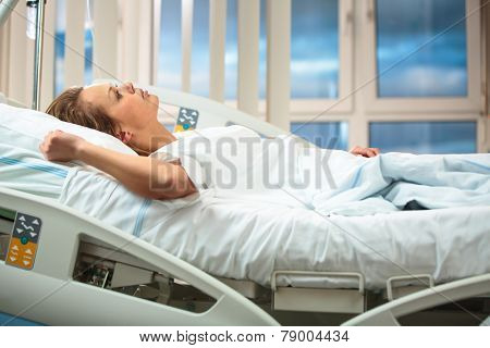 Pretty, young, female patient in a modern hospital room. Getting better fast after a surgery - pensive yet positive, thinking ahead, making plans (shallow DOF; color toned image) stock photo