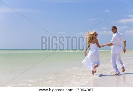 Happy young man and woman couple running laughing and holding hands on a deserted tropical beach with bright clear blue sky stock photo