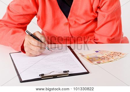 A senior woman's hand signing on a document stock photo