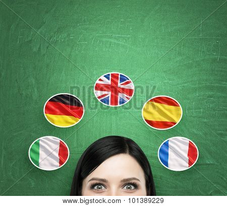 A concept of foreign language studying process. A foreseen of the brunette girl surrounded by icons of european flags. Green chalkboard background. stock photo