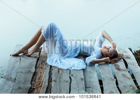 Gentle girl in white dress lying on a wooden pier. She was barefoot. stock photo