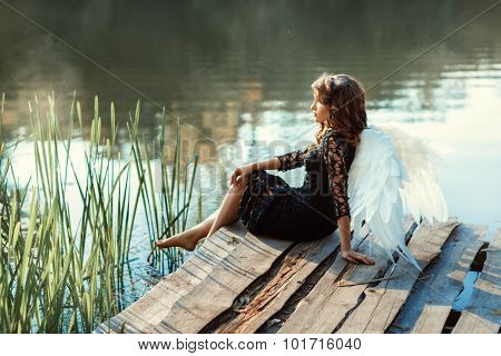 On the pier near the river sits a girl angel. Her black dress and white wings. See more photos of this series. stock photo