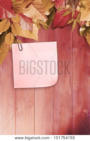 Sticky note with grey paperclip against autumn leaves pattern stock photo
