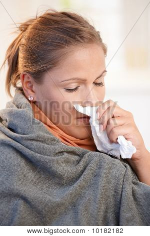 Young woman caught cold feeling bad blowing her nose wrapped up in blanket. stock photo