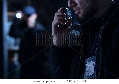 Officer using walkie talkie during police intervention stock photo