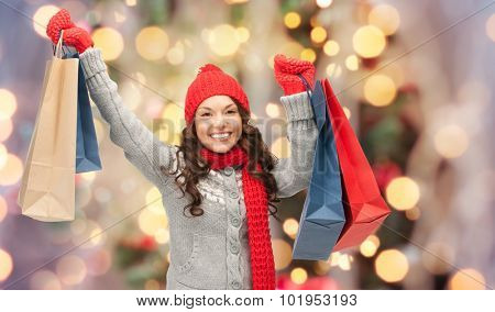 holidays, x-mas, sale and people concept - happy young asian woman in winter clothes with shopping b