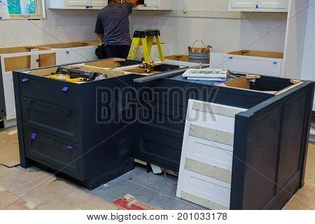Repair man In Overalls Repairing Cabinet Hinge In Kitchen Installation of kitchen. Worker installs doors to kitchen cabinet. stock photo
